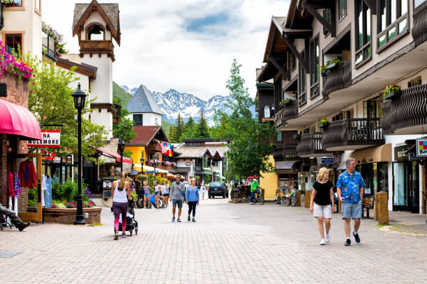 Vacation resort town of Vail, Colorado with people walking shopping by shops on Gore Creek drive stock photo