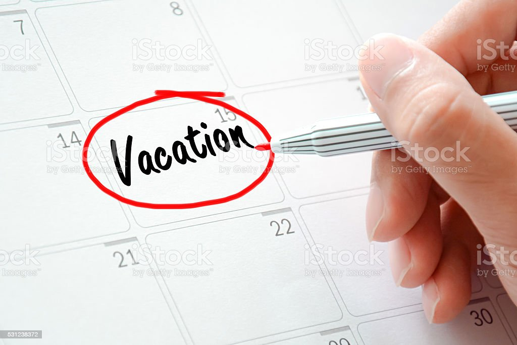 Vacation text on desk plannercircled with red marker stock photo