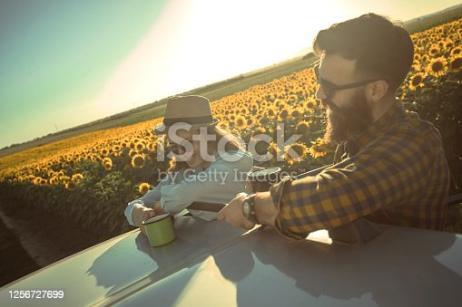 An image depicting two happy young people having a coffee on the car roof, while enjoying the sunset in the middle of sunflower field.