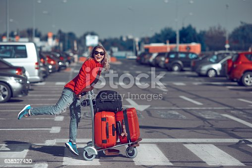 lifestyle shot of happy woman carrying her luggages, laughing and feeling great in her vacation.