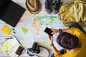 Vacation travel planning concept with map. Overhead view of equipment for travelers. Travel concept background, young Asian woman. Travel holiday, summer.