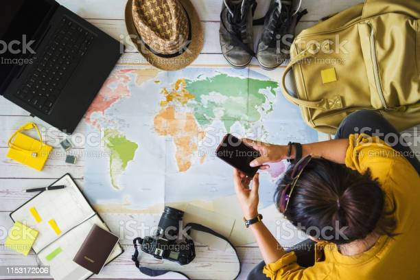 Photo of Vacation travel planning concept with map. Overhead view of equipment for travelers. Travel concept background, young Asian woman. Travel holiday, summer.