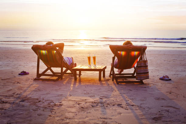 Vacation travel, silhouettes of happy couple relaxing on beach. honeymoon travel, silhouettes of happy couple relaxing in deck chairs on the beach at sunset retirement stock pictures, royalty-free photos & images