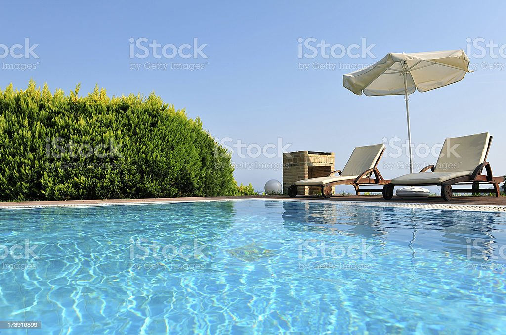 Vacation villa swimming pool, sun lounger area and barbecue. stock photo