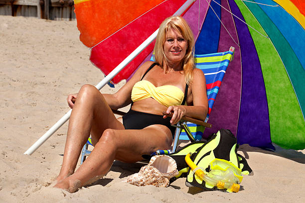 Vacation: Woman Enjoying the Beach Woman enjoying a day at the beach with snorkeling gear,sitting a a lounge chair under a colorful rainbow striped umbrella middle aged women in bikinis stock pictures, royalty-free photos & images