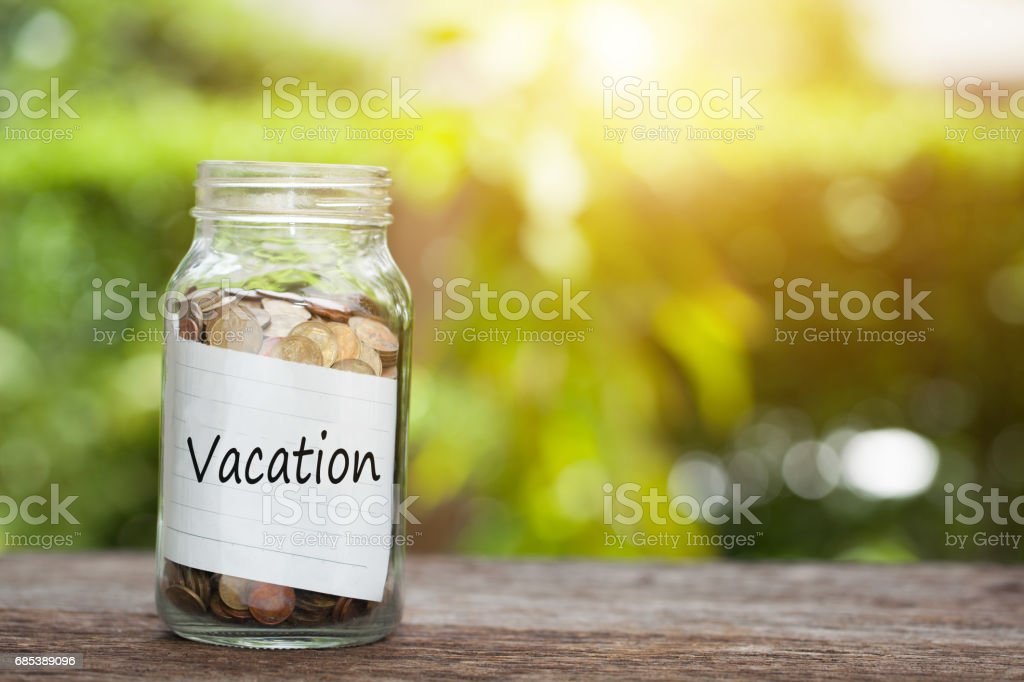 vacation word with coin in glass jar on wooden table. foto de stock royalty-free