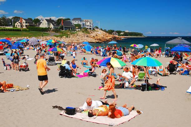 Urlauber drängen sich an einem sonnigen Tag am Strand – Foto