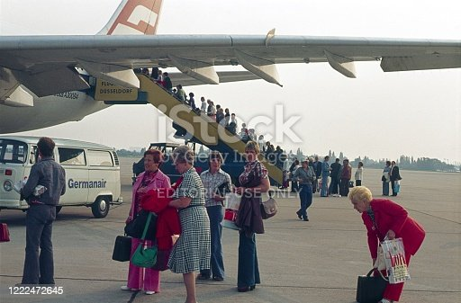 Düsseldorf, North Rhine-Westphalia, Germany, 1976. All-inclusive vacationers board a charter plane on the airfield of Düsseldorf Airport.