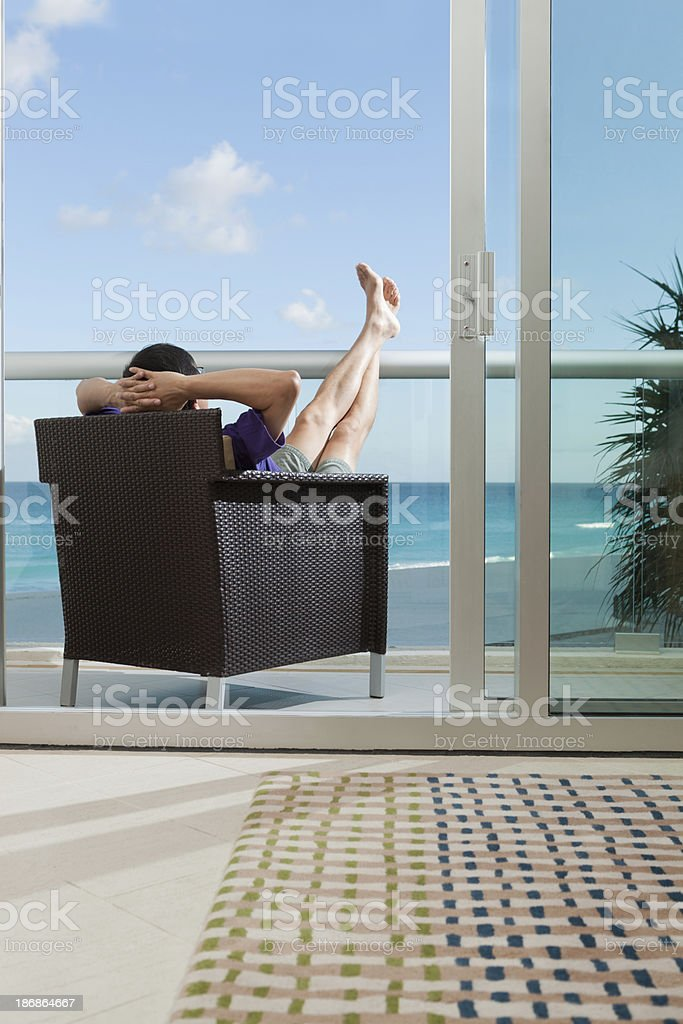 Vacationing Asian Man Relaxing in Balcony of Tropical Resort Hotel_ royalty-free stock photo
