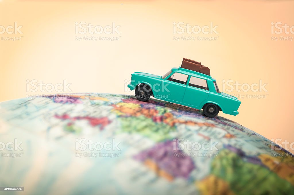 Vacationing toy car on a globe stock photo