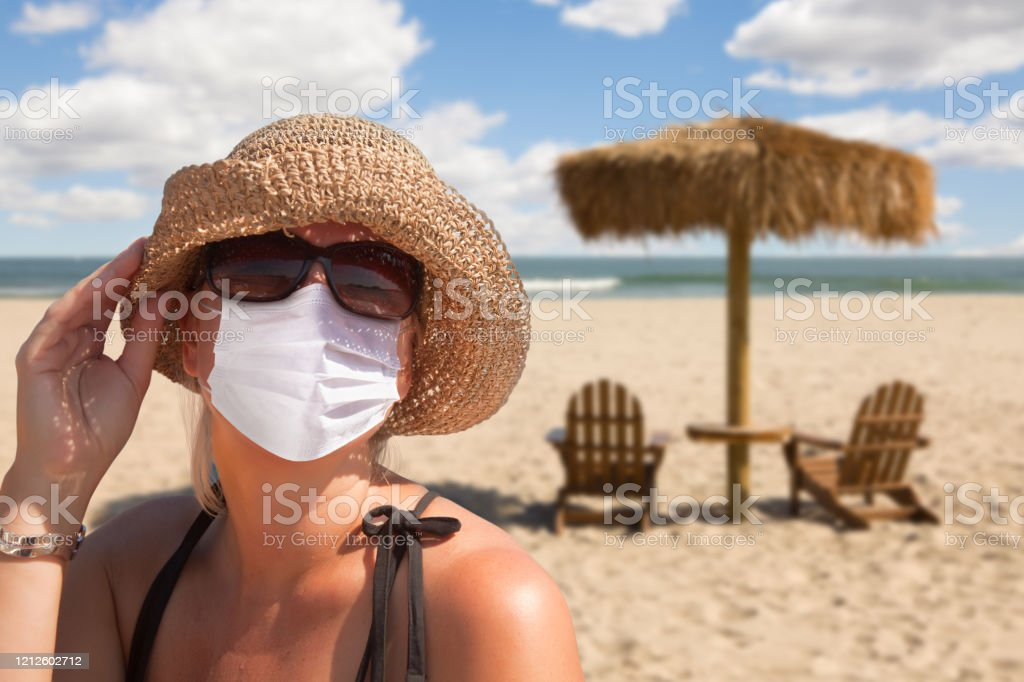 Vacationing Woman Wearing Face Mask on Sandy Beach. Vacationing Woman Wearing Face Mask on Sandy Beach.. Adult Stock Photo