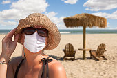 Vacationing Woman Wearing Face Mask on Sandy Beach..