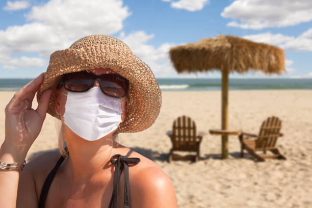 Vacationing Woman Wearing Face Mask on Sandy Beach. stock photo