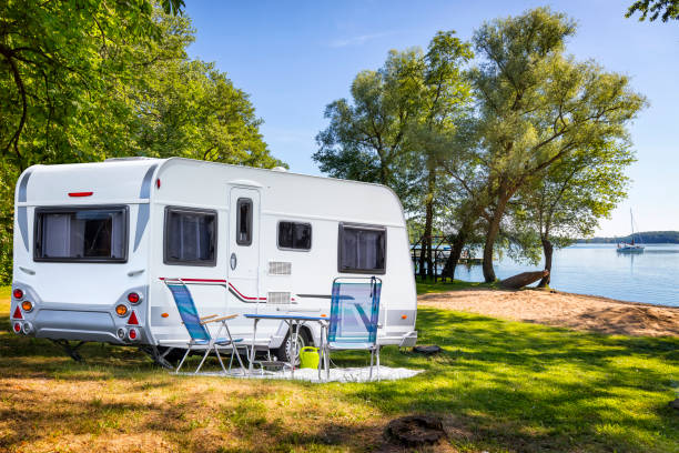 Vacations in Poland - Camper trailer on the shore of bay of the Drawsko lake Vacations in Poland - Camper trailer on the shore of bay of the Drawsko lake caravan photos stock pictures, royalty-free photos & images