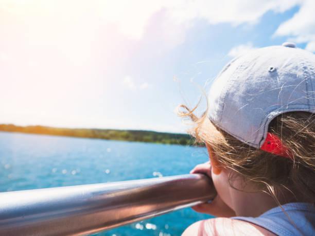 Ferien: Kleines Mädchen auf der Suche über den Bodensee auf einem Boot stehend – Foto