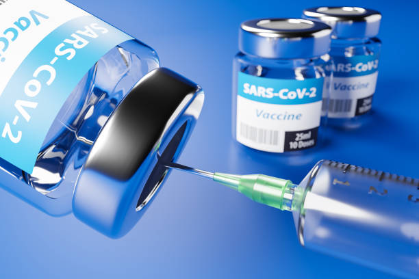 Vaccination against the new Corona Virus SARS-CoV-2: Two glass containers with 10 doses each and a syringe in front. Selective focus on foreground. stock photo
