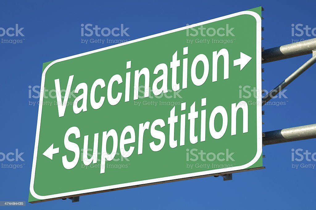 Vaccination VS Superstition Highway Sign stock photo