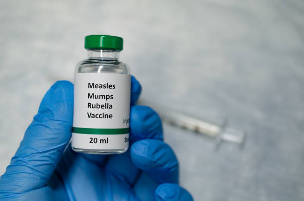 MMR vaccine holding in hand with injection syringe at the background A fake MMR vaccine vial holding in hand measles stock pictures, royalty-free photos & images