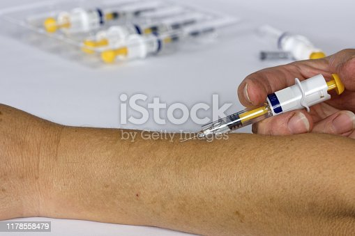 917598714istockphoto Vaccine or flu shot in injection needle. Doctor working with patient's arm. Physician or nurse giving vaccination and immunity to virus 1178558479