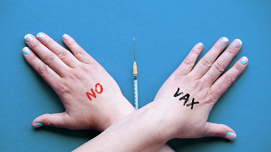 Vaccine refusal concept. Crossed hands with text No Vax over vaccination syringe. Person refusing vaccination from measles, Covid-19. Anti-vaccination concept with refusal gesture on blue paper.