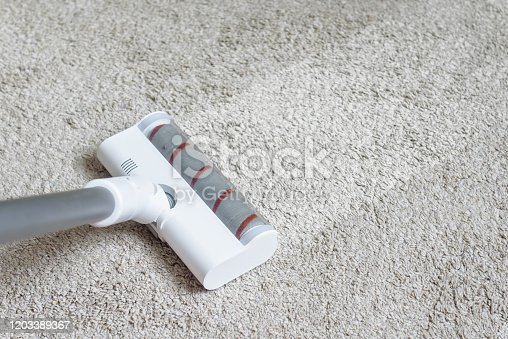 Vacuum cleaner head on dirty carpet with clean strip. Housework with using hoover. Turbo brush of modern vacuum cleaner close up. Home cleaning and care concept for background.