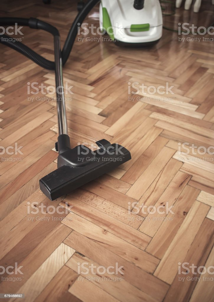 Vacuum cleaner on parquet royalty-free stock photo