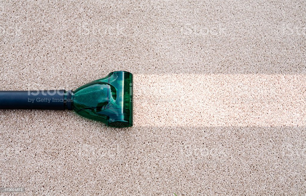 A vacuum cleaning a dirty carpet stock photo