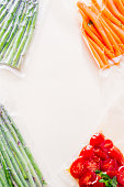 Vacuum sealed vegetables , carrots, asparagus, tomato,  on a gray background top view, ready o be cooked with sous vide rooner