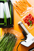 Vacuum sealed vegetables , carrots, asparagus, tomato,  on an orange background top view, ready to be cooked with sous vide rooner, with a automatic vacuum sealer machine and a rooner