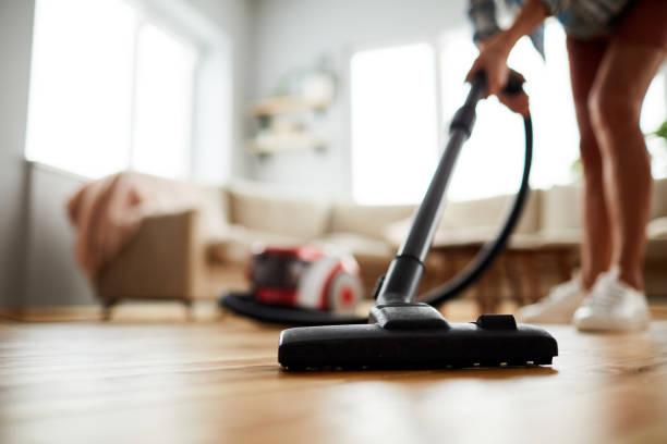 Vacuuming floor at home stock photo