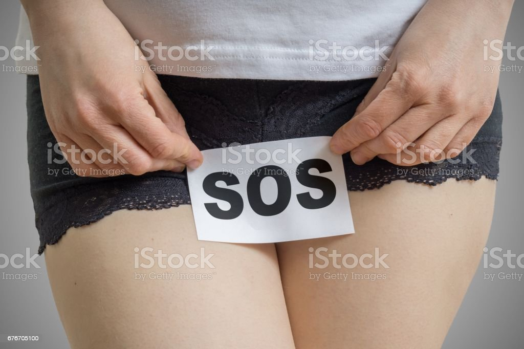 Vaginal or menstrual problems concept. Young woman holds paper with SOS above crotch. stock photo