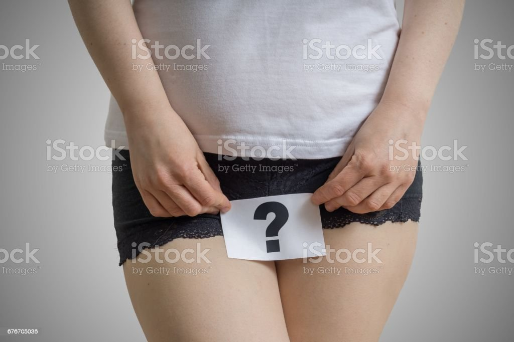 Vaginal or urinary infection and problems concept. Young woman holds paper with questionmark above crotch. stock photo