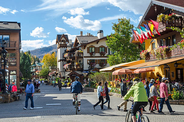 Vail Village in Vail, Colorado Vail, Colorado, USA - October 11, 2015: Residents and tourist walk and ride bikes on a beautiful Fall afternoon through the luxurious resorts, condominiums, chalets, shops and restaurants in the famous ski village of Vail, Colorado. The village was established in 1962 and built as the base village to Vail Ski Resort, with which it was originally conceived and is the third largest ski mountain in North America. Vail attracts wealthy visitors, many of whom, who build and purchase vacation homes and condominiums near the ski slopes. Street view of the village and Gore Creek Drive was taken in Vail, Colorado near the Eagle Bahn Gondola. vail colorado stock pictures, royalty-free photos & images