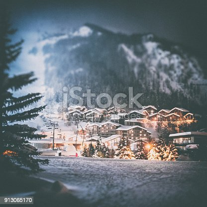 Color dark photography of Val d'isere ski resort illuminated village by snowy night in European Alps in winter, with some deep snow and ski lift equipements lost in fog. This image was taken in winter season in Val d'Isere, a french famous ski resort village in Tarentaise mountains, in Savoie, Auvergne-Rhone-Alpes region in European Alps.