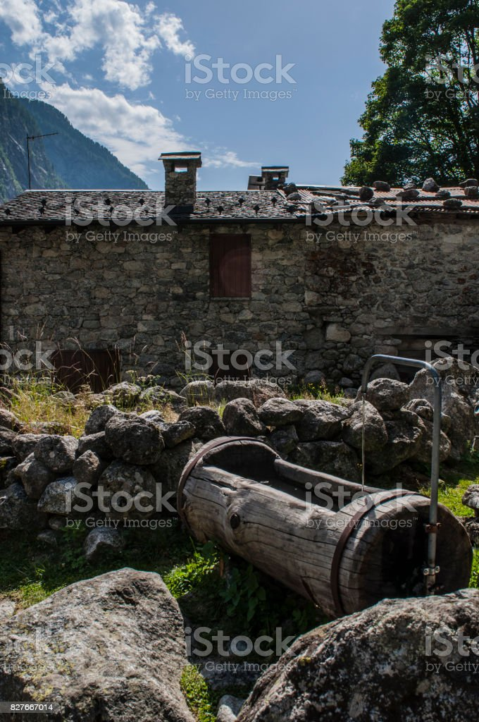 Val Masino: a wooden fountain of spring water in the Val di Mello, green valley surrounded by granite mountains and forest trees stock photo