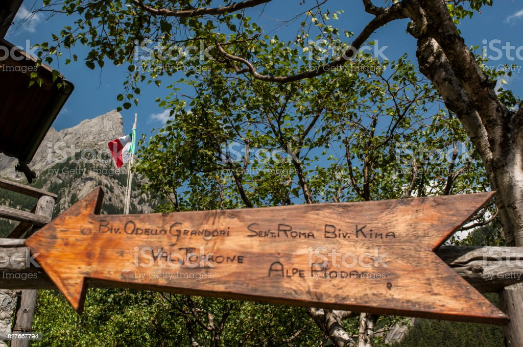 Val Masino: an italian flag and the wooden sign for Mount Pioda, one of the peaks of the Val di Mello, green valley surrounded by granite mountains and forest tree stock photo
