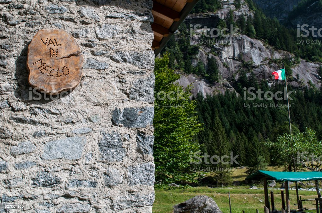 Val Masino: an italian flag and the wooden sign of the Mello Valley, Val di Mello, a green valley surrounded by granite mountains and forest trees stock photo