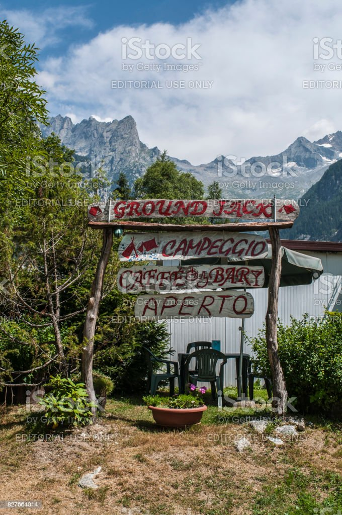 Val Masino: the wooden sign of Ground Jack, the camping of the Val di Mello, green valley surrounded by granite mountains and forest trees, stock photo