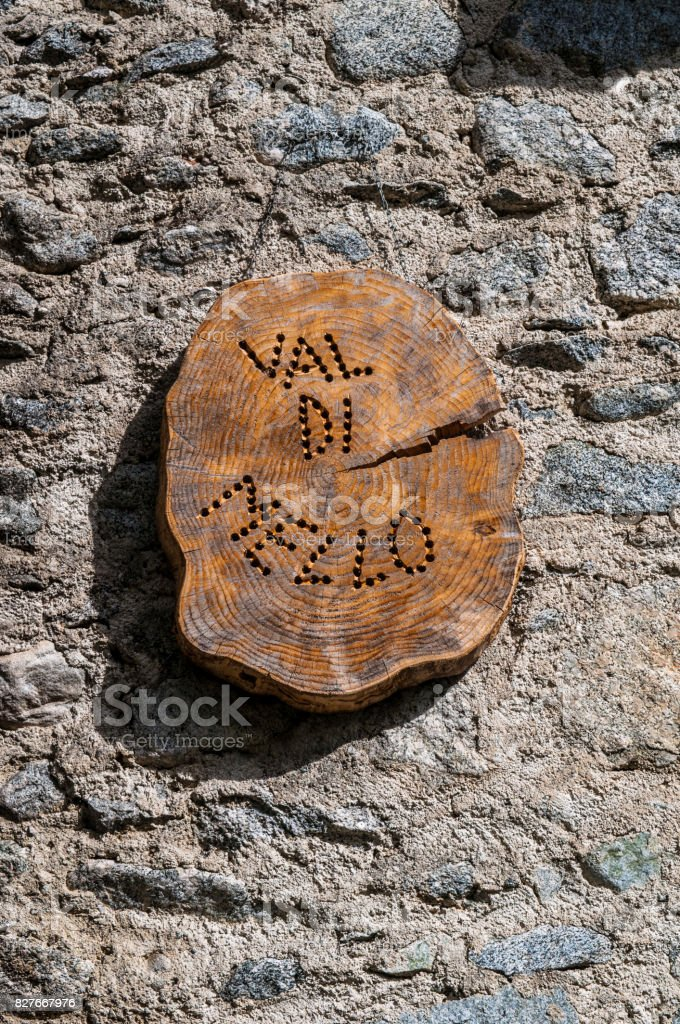 Val Masino: the wooden sign of the Mello Valley, Val di Mello, a green valley surrounded by granite mountains and forest trees stock photo