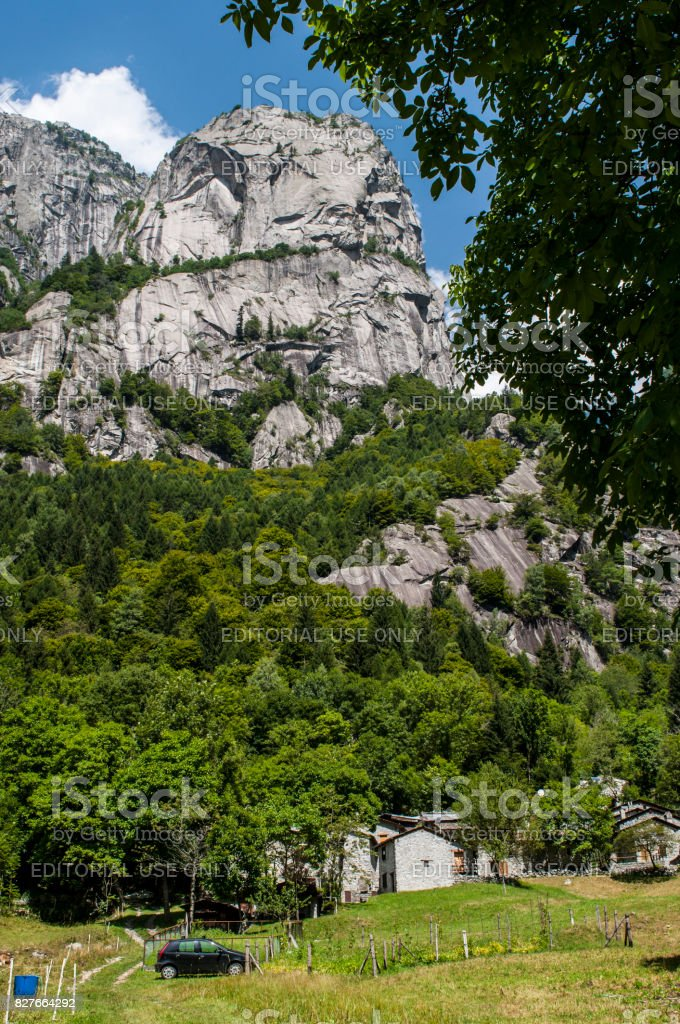 Val Masino: view of a house at the bottom of the mountain peaks of the Mello Valley, Val di Mello, a green valley surrounded by granite mountains and forest trees stock photo