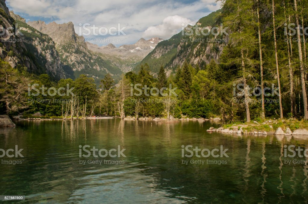 Val Masino: view of the alpine lake in the Mello Valley, Val di Mello, a green valley surrounded by granite mountains and forest trees stock photo