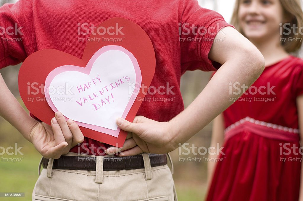 Valentine card behind boys back for girl royalty-free stock photo
