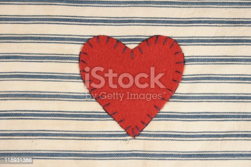 Appliqued Red Felt Heart On Blue and White Striped Cotton Ticking Fabric Cloth Background for Valentine's Day with room for text.