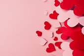 Valentine day background of fly paper red and pink hearts on pink color backdrop. Copy space.