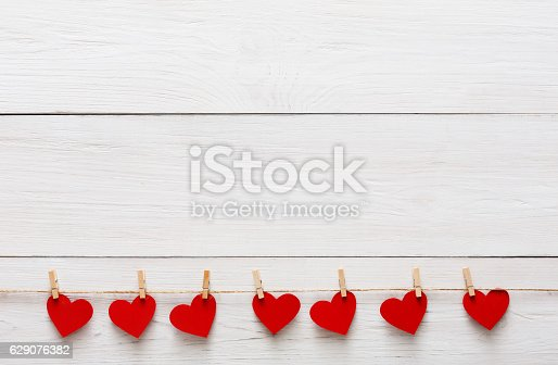 Valentine background with red paper hearts row border on clothespins on white rustic wood planks. Happy lovers day card mockup, copy space