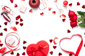 Valentine day composition with red gift box, bow and small hearts on white background. Top view.