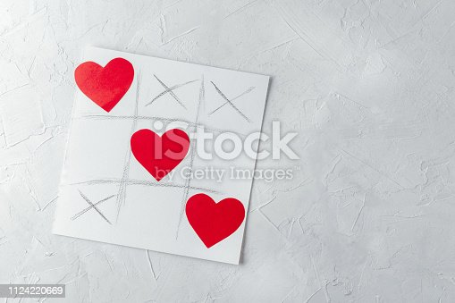 Valentine day concept, greetings card - tic tac toe game with hearts, white concrete wall, copy space