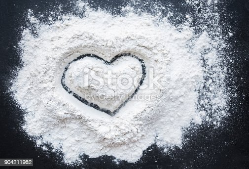 istock Valentine Day Concept idea image - Heart shape in a baking flour on black background. Cooking love recipe concept 904211982