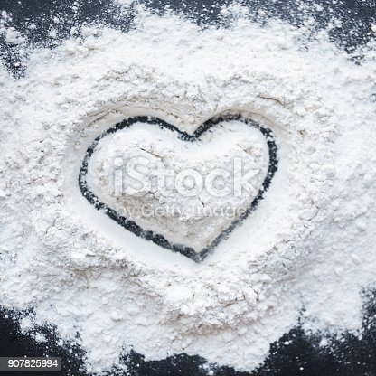 istock Valentine Day Concept idea image - Heart shape in a baking flour on black background. Cooking love recipe concept 907825994