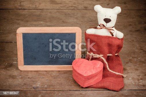 678159134 istock photo Valentine heart shape box, handmade bear, black board 162165347